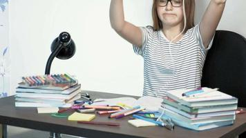 A teenager girl with glasses is sitting at a school desk learning concept video