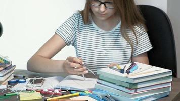 uma adolescente com óculos está sentada em uma mesa de escola, aprendendo o conceito video