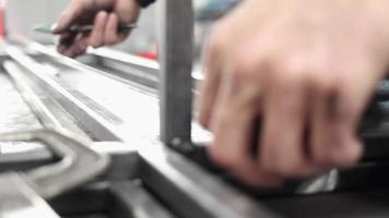 A man measuring steel bars together to create a structure in a machine shop. video