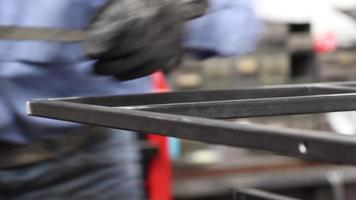 A man filing steel bars together to create a structure in a machine shop. video