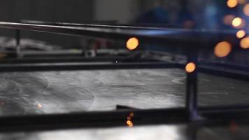un homme soude des barres d'acier pour créer une structure dans un atelier d'usinage. video
