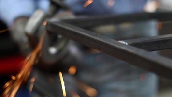 un homme meulant de l'acier pour créer une structure dans un atelier d'usinage. video