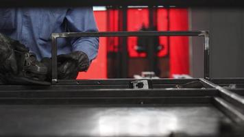 A man grinding steel to create a structure in a machine shop. video