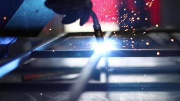 un hombre soldando barras de acero juntas para crear una estructura en un taller mecánico. video