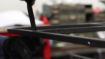 un hombre archivando barras de acero juntas para crear una estructura en un taller mecánico. video