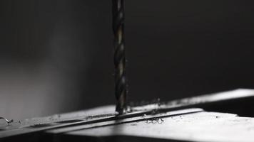 Detalle de barras de acero perforadas por una taladradora para crear una estructura en un taller de maquinaria. video