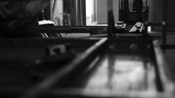 un hombre trabaja con barras de acero juntas para crear una estructura en un taller de máquinas. video