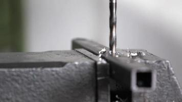 Detail steel bars being drilled by a drill press to create a structure in a machine shop. video
