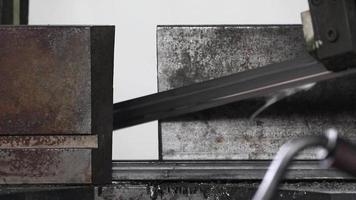 Detalle de barras de acero cortadas por una sierra para crear una estructura en un taller mecánico. video