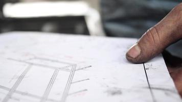 um homem desenha com uma caneta em planos de projeto. video