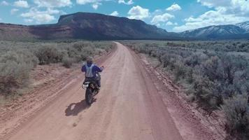 Aerial drone view of a motocross motorcycle driving off-road on a dirt road in Moab, Utah. video
