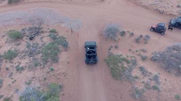 luftdrohnenansicht eines 4x4-fahrzeugs, das auf einer unbefestigten straße in moab, utah, im gelände fährt. video