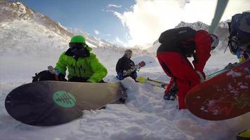un aterrizaje de helicóptero para recoger a los esquiadores para esquiar y hacer snowboard en las montañas. video