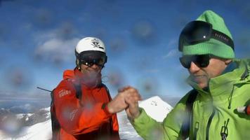 los esquiadores chocan los cinco antes de esquiar en las montañas. video