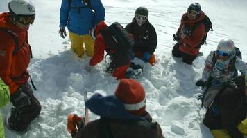 helicóptero descarga esquiadores y practicantes de snowboard en las montañas. video