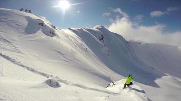 un fotógrafo fotografiando esquiadores esquiando en montañas cubiertas de nieve. video