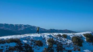 en man går kör på toppen av snötäckta berg. video