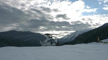 El helicóptero despega después de dejar a los esquiadores para esquiar en las montañas. video
