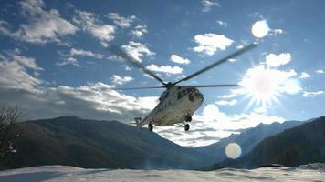 un helicóptero aterriza para recoger a los esquiadores en las montañas. video