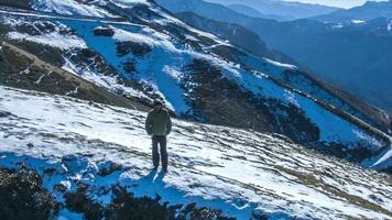 un hombre camina corre en la cima de montañas cubiertas de nieve. video