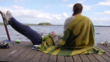 mujeres adultas jóvenes niñas relajarse en un muelle del lago. video