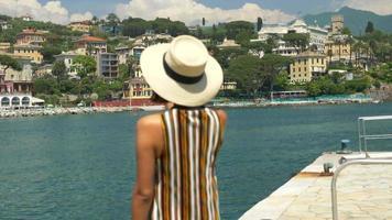 una donna con un cappello scatta foto mentre viaggia in una località turistica di lusso in italia, europa. video