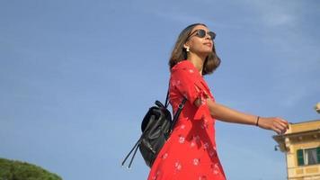 una donna che cammina in un abito rosso in una località turistica di lusso in italia, europa. video