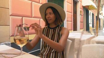 una donna beve vino quando viaggia in una località turistica di lusso in italia, europa. video