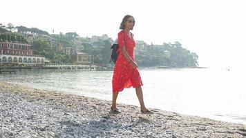 una donna cammina su una spiaggia in un vestito rosso mentre viaggia in una località turistica di lusso in italia, europa. video