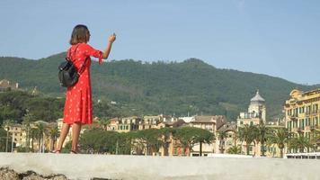una donna con un vestito rosso scatta foto mentre viaggia in una località turistica di lusso in italia, europa. video