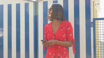 una donna che invia messaggi e sms quando si viaggia in una località turistica di lusso in italia, europa. video