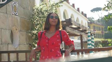 una donna in abito rosso che viaggia in una località turistica di lusso in italia, europa. video