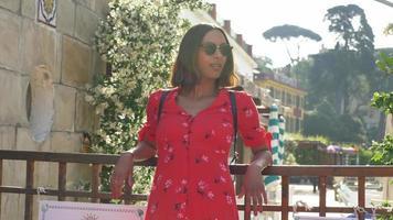 una mujer con un vestido rojo que viaja en una ciudad turística de lujo en Italia, Europa. video