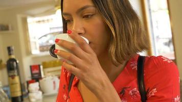 una donna in viaggio beve caffè cappuccino espresso in un bar. video