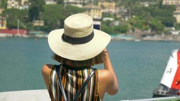 Una mujer con sombrero toma fotografías mientras viaja en una ciudad turística de lujo en Italia, Europa. video
