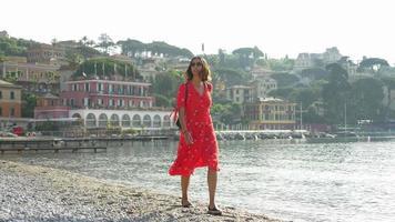 uma mulher caminha em uma praia com um vestido vermelho enquanto viaja em uma cidade turística de luxo na itália, europa. video