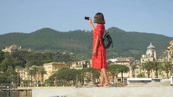 Una mujer con un vestido rojo toma fotografías mientras viaja en una ciudad turística de lujo en Italia, Europa. video