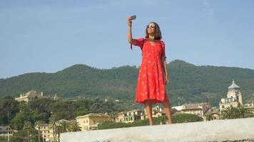 Una mujer se toma selfies mientras viaja en una ciudad turística de lujo en Italia, Europa. video