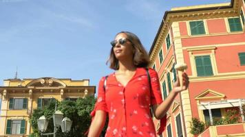 A woman eating gelato ice cream while traveling in a luxury resort town in Italy, Europe. video