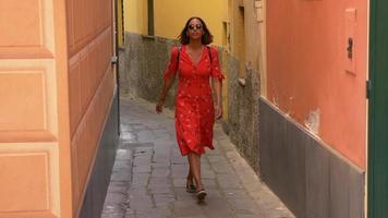 en kvinna som går i en röd klänning i en lyxig semesterort i Italien, Europa. video