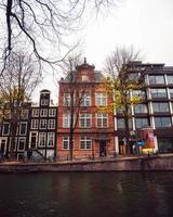 Amsterdam, Netherlands 2018- A row of buildings behind a river canal in Amsterdam photo