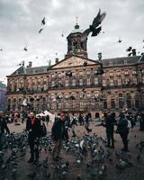 Amsterdam, Netherlands 2018- A group of people with pigeons in front of the Royal Palace in Amsterdam photo