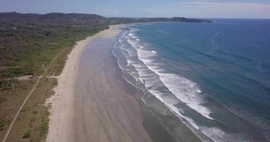 Aerial drone view of the beach, rocks and tide pools in Guiones, Nosara, Costa Rica. video