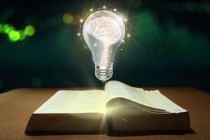 cerebro dentro de la bombilla flotando en el libro. foto