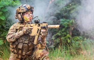 Portrait woman soldier shooting with rifle machine gun Maneuver in the forest photo