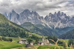 Pueblo de Santa Maddalena con hermosas montañas Dolomitas en el fondo, Val di Funes Valley, Italia foto