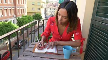 A woman writing in a journal diary traveling in a luxury resort town in Italy, Europe. video