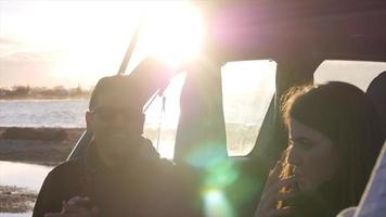um jovem casal sentado na parte de trás de um carro SUV. video