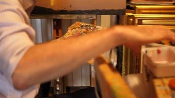 detalhe da mão de um artista e paleta de tintas enquanto ele pinta uma pintura a óleo sobre tela dentro de seu estúdio de arte. video
