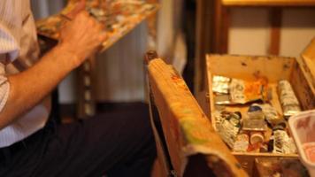 detalhe da mão de um artista e paleta de tinta enquanto ele pinta uma pintura a óleo sobre tela dentro de seu estúdio de arte. video